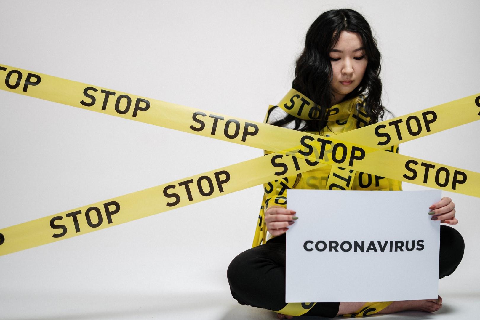 Woman holding sign that says stop corona virus